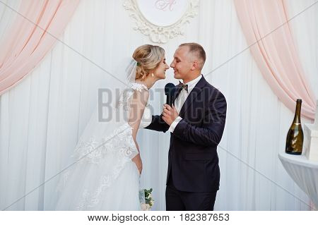 Bride And Groom Kissing After Speech At Wedding Ceremony.