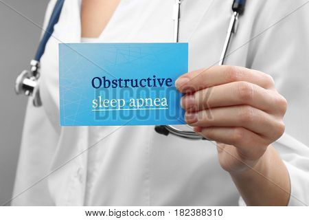 Doctor holding card with text OBSTRUCTIVE SLEEP APNEA, closeup