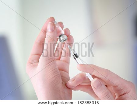 Hands of doctor with syringe and medicine in clinic, closeup