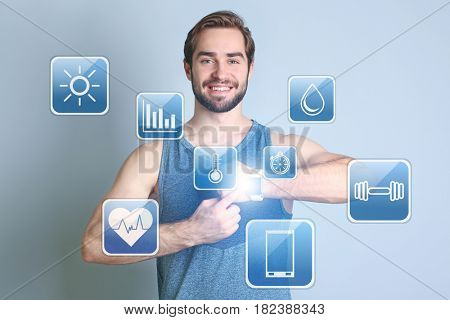 Sport application concept. Young woman with fitness tracker on blue background