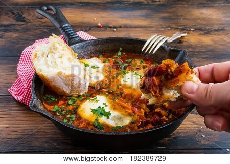 Traditional Arabic dish shakshuka in a black cast iron pan and pepper on the wooden brown background.