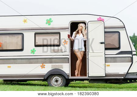 Young and beautiful hippy girl standing in trailer door. Holiday, journey, vacation concept.