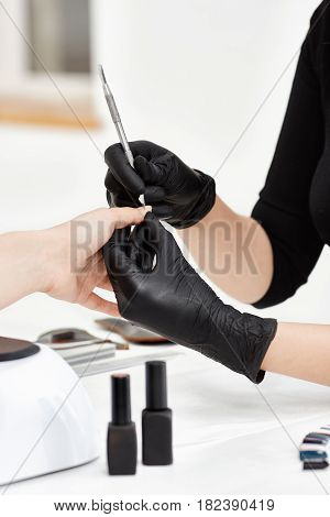 Vertical shot of manicurist removing cuticle with special tool working at bright nail salon.