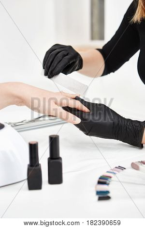 Manicurist filing nails doing manicure at salon. Professional manicure tools and polish set on table.