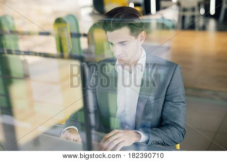 Successful Entrepreneur Smiling In Satisfaction As He Checks Information On His Laptop Computer Whil