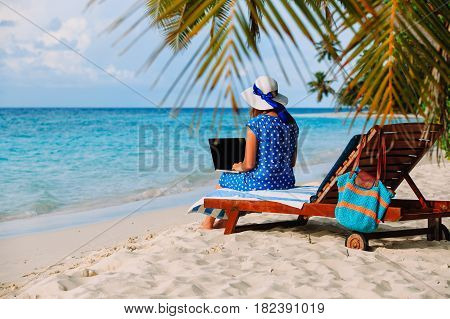 remote work cocept -woman with laptop on tropical beach