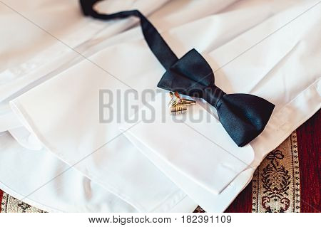 bowtie and cufflinks on a white shirt. Grooms morning