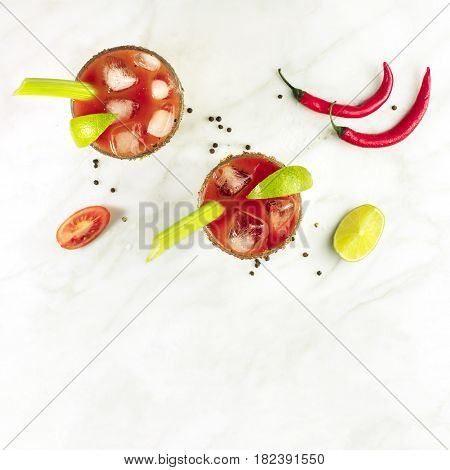 A square photo of Bloody Mary cocktails, shot from above on a white marble texture, with red hot chili peppers, slices of lime, celery sticks, a piece of tomato and copyspace