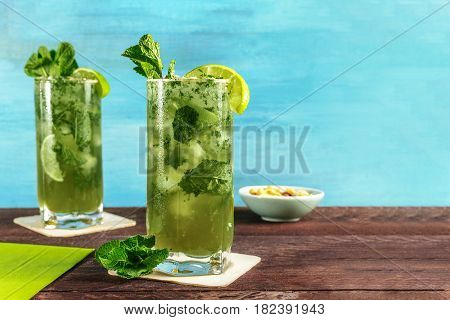 A photo of mojito cocktails with mint leaves, wedges of lime, and a snack, on a vibrant turquoise wooden background with copy space. Selective focus