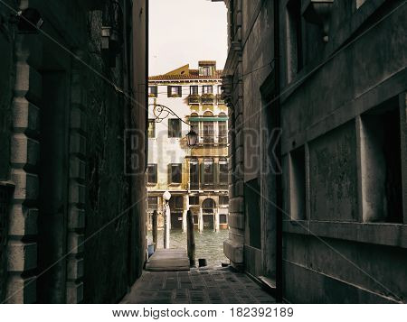 Narrow passage in Venice streets leading to water