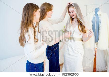 Pretty bride chooses bridal veil at shop of wedding fashion