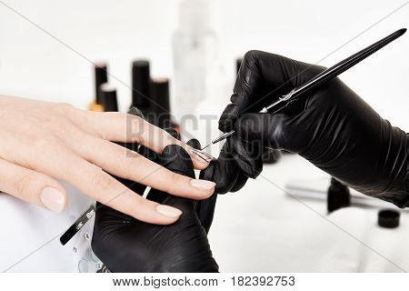 Closeup of profesional manicurist doing trendy nail art with thin manicure brush at bright salon.