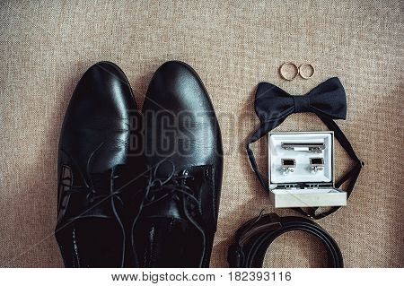 Close up of modern man accessories. wedding rings, black bowtie, leather shoes, belt and cufflinks. Selective focus. Look from above