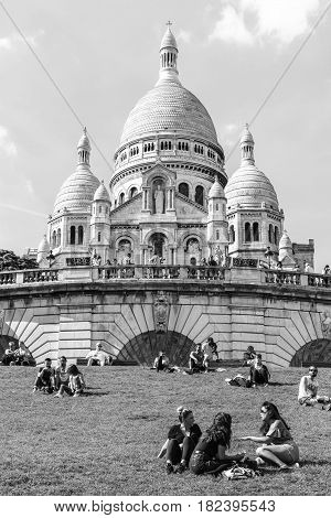 Paris France - July 06 2016: Tourists sitting on the grass near Basilica Sacre Coeur on Montmartre hill in the sunny summer day. Black and white.