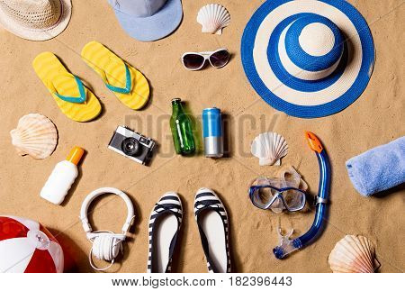 Summer vacation composition with a pair of yellow flip flop sandals, hat, sunglasses, goggles, sunscreen and other stuff on a beach. Sand background, studio shot, flat lay.