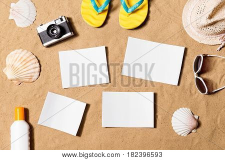 Summer vacation composition with pair of yellow flip flop sandals, hat, sunglasses, sun cream, empty paper cards and other stuff on a beach. Sand background, studio shot, flat lay. Copy space.