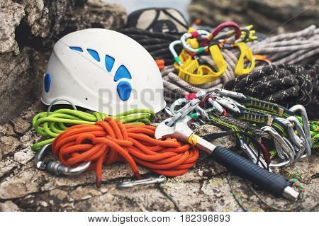 Used climbing equipment - carabiner without scratches, climbing hammer, white helmet and grey, red, green and black rope on the stone