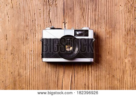 Summer vacation composition. Vintage camera laid on table. Wooden background. Studio shot, flat lay. Copy space.