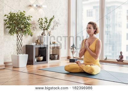 Meditation brings balance to my life. Portrait of relaxed young woman sitting in lotus position with happy smile