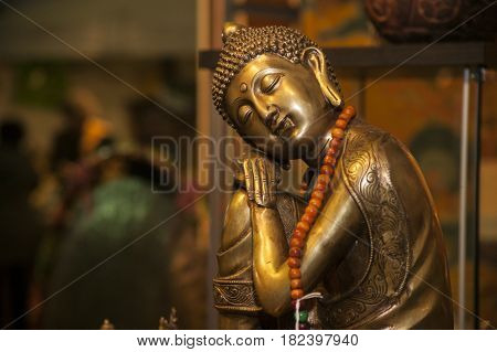 Spiritual Bronze statuette of a small buddha spiritual figure in a stall at a trade fair.