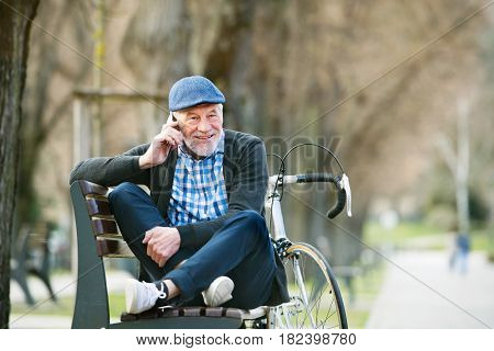 Handsome senior man with bicycle in town park sitting on bench with legs crossed, holding smart phone, making phone call. Sunny spring day.