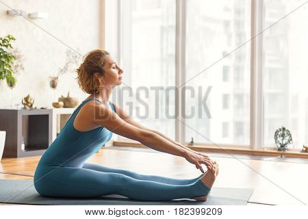Calm young woman is warming up her body before training. She is sitting and stretching arms to legs. Her eyes are closed