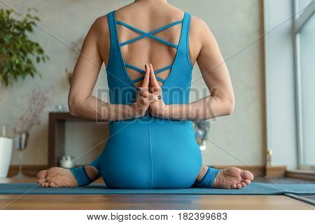 Close up of fit body of young woman doing yoga. She is sitting and joining hands behind her back. Girl is wearing blue sportswear