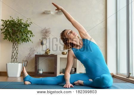 Portrait of confident young woman is doing exercise at home. She is sitting on mat and stretching arm up