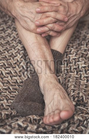 Man Feet On Woolen Plaid In One Woolen Sock