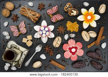 Gingerbread cookies with cup of coffee, nuts, dates and spices, colorful homemade cakes in shape of flower and butterfly on black textured background, top view