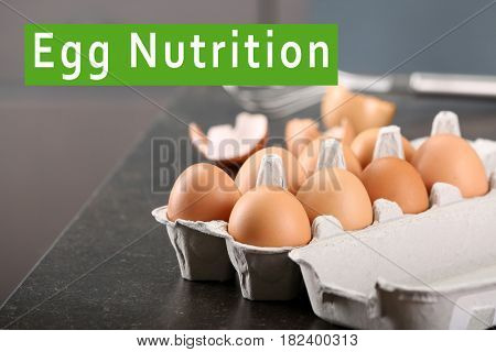 Cardboard package with eggs on table. Text EGG NUTRITION on background