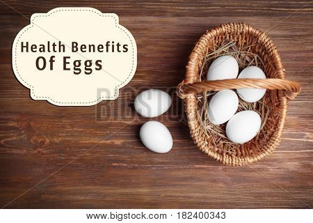 Eggs and wicker basket on wooden background. Text HEALTH BENEFITS OF EGGS