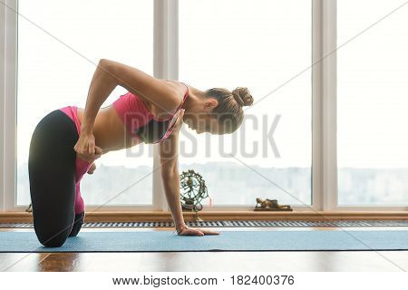 Professional female athlete is doing exercise for flexibility. She is kneeling and bending foot sideways with efforts. Copy space in right side