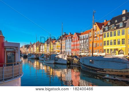 COPENHAGEN DENMARK - MARCH 11 2017: Tourists in Copenhagen Nyhavn district. The famous Danish fairytale writer Hans Christian Andersen used to live in no. 20
