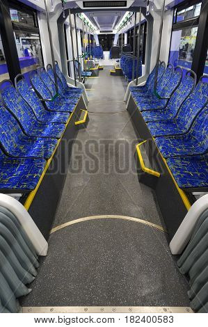 Tram inside, city transportation interior with blue seats in row, chrome handles for standing passengers and bright lights
