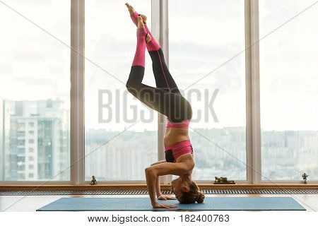 Skillful female athlete is standing on her head while leaning hands on mat. She is stretching feet up with concentration