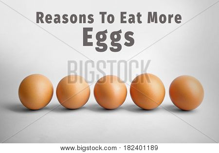 Raw eggs on light background. Text REASONS TO EAT MORE EGGS