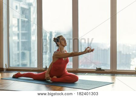 Professional yoga technique. Peaceful young woman is sitting on string while holding foot by hand through back. She is stretching hand forward with serenity