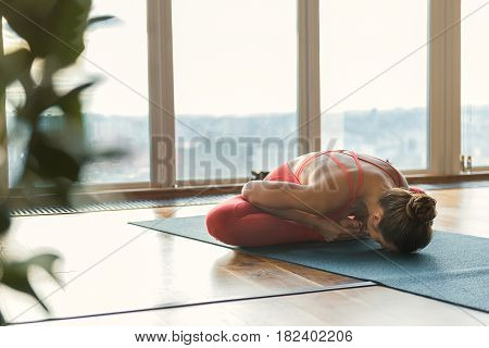 Calm young woman is doing yoga in gym. She is sitting in lotus position near large window and reaching head to floor