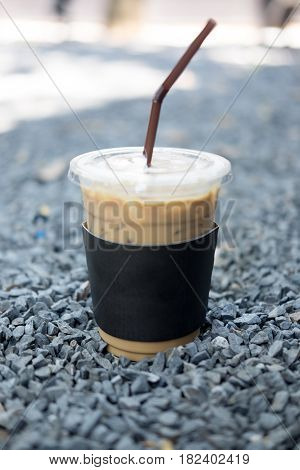 Cold coffee in plastic cup on stone