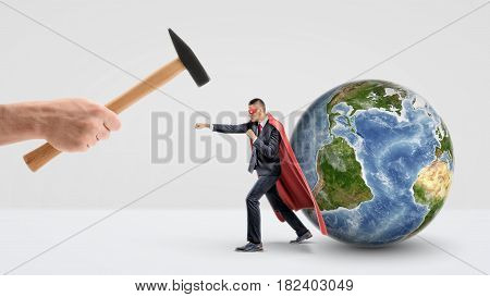 A businessman in a red superhero cape protecting a small globe behind him and punching a giant hand holding a hammer. International business. Corporate hero. Big and small companies.
