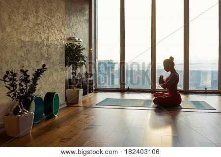 Healthy young woman is relaxing during meditation. She is sitting in lotus position on mat and joining hands together. Large window with city view on background