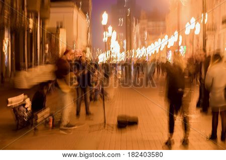 Abstract vintage tone motion, blurred image of street musicians, spectators and bright city lights with bokeh, night urban street life, motion blur concept, for background use