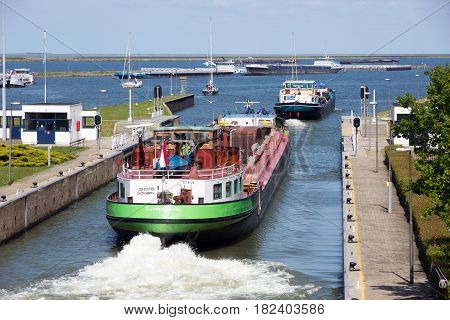 ENKHUIZEN THE NETHERLANDS - MAY 15 2014: Barge ships passing through the Enkhuizen sluice.