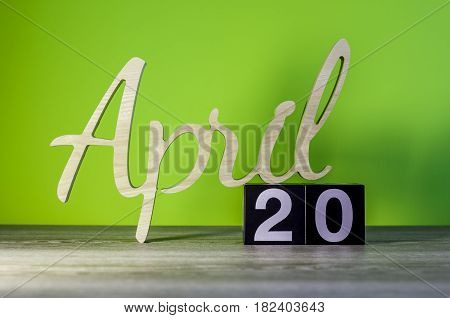 April 20th. Day 20 of month, calendar on wooden table and green background. Spring time, empty space for text.