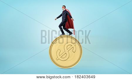 A businessman in a red superhero cape balancing on the edge of a giant golden coin with a USD sign. Money and investment. Financial wisdom. Business risks.