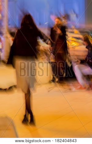 Abstract vintage tone motion, blurred image of street musiciant and young girl the spectator with her back to us. Night urban street life, motion blur concept, for background use