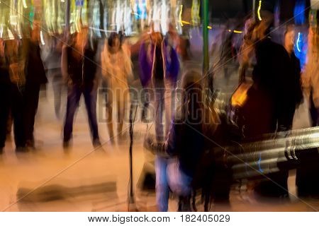 Abstract vintage tone motion, performance on the street, blurred image of street musicians and young Spectators, pedestrians. Night urban street life, motion blur concept, for background use