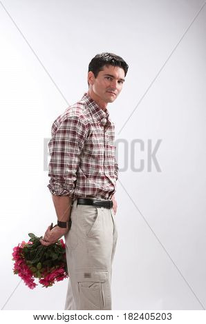 The attractive man is holding flowers behind his back.