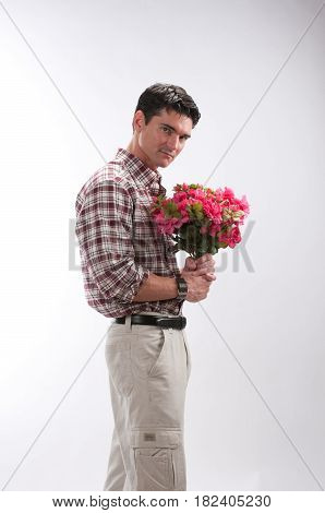The adorable man is holding some flowers.
